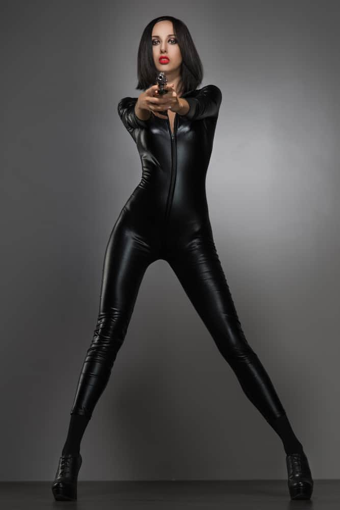 A woman wearing a black latex catsuit.