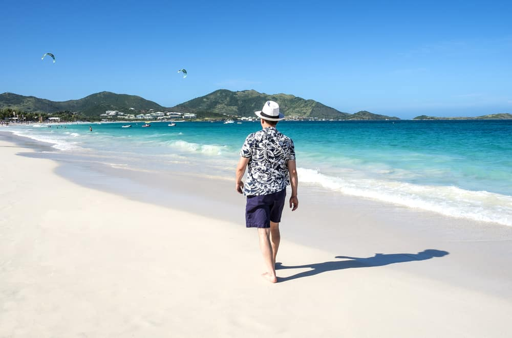 A man wearing a Hawaiian shirt at the beach.