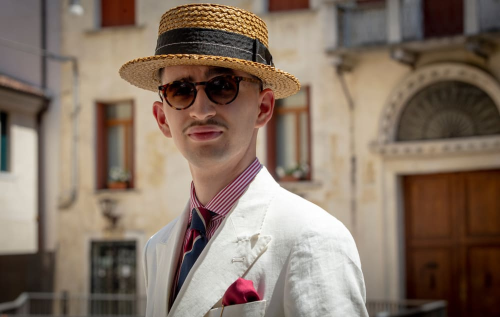 A man wearing a suit and a straw boater hat.