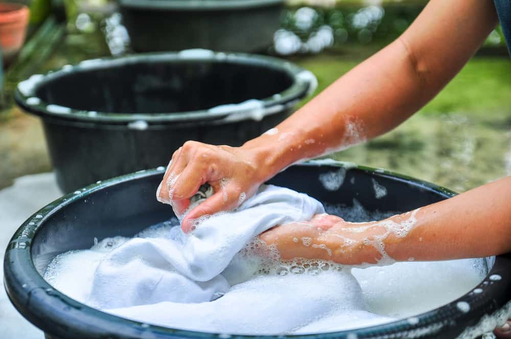 A person hand-washing the clothes on a basin.