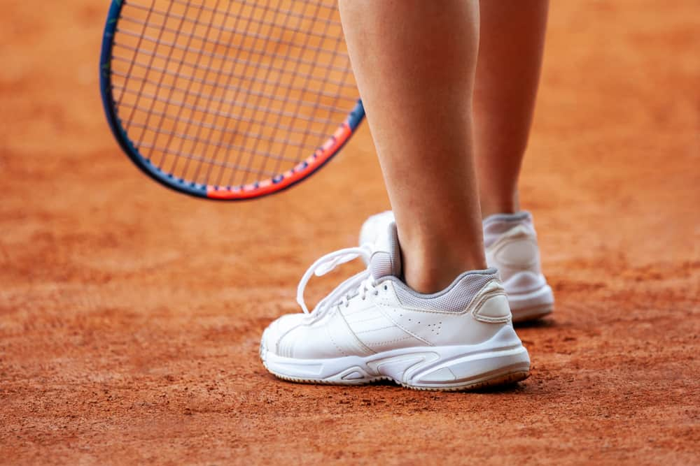 A close look at a tennis player wearing a pair of court shoes.