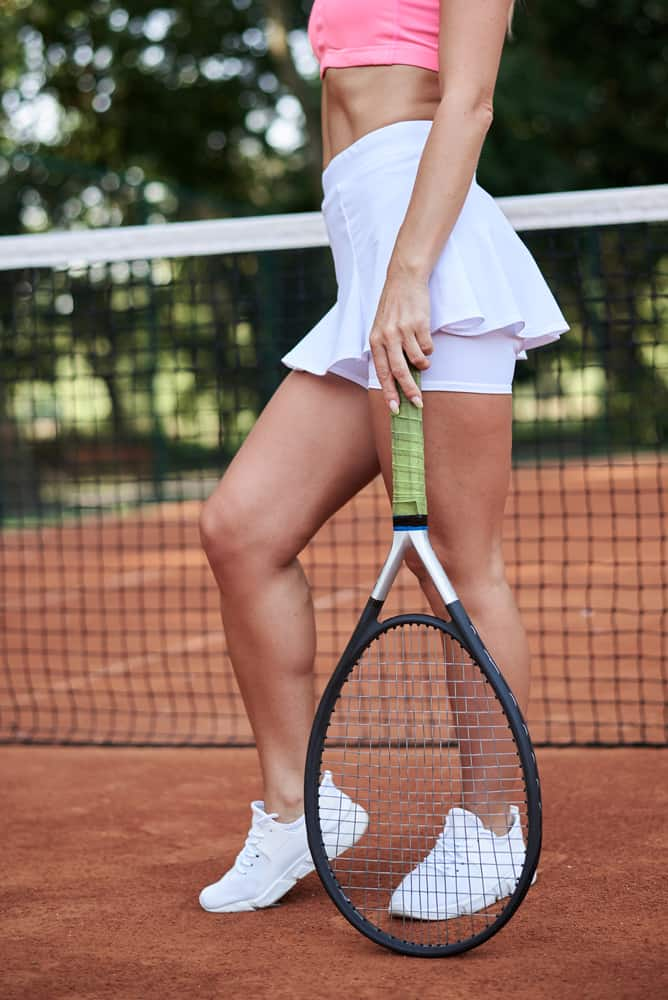 A close look at a tennis player wearing a white skirt.