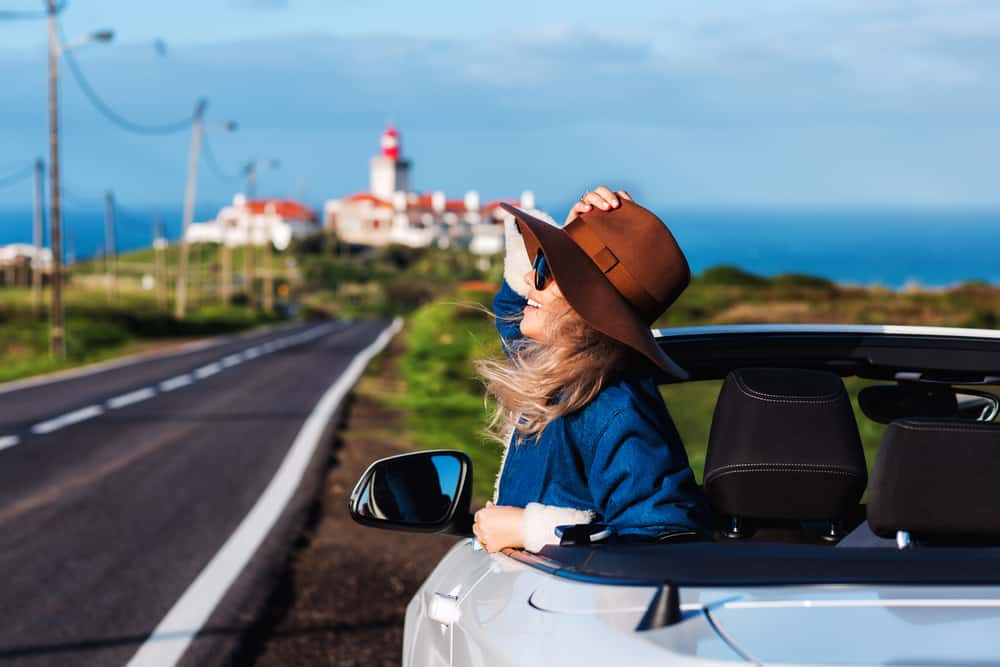 A woman wearing a fedora hat while riding a convertible car.