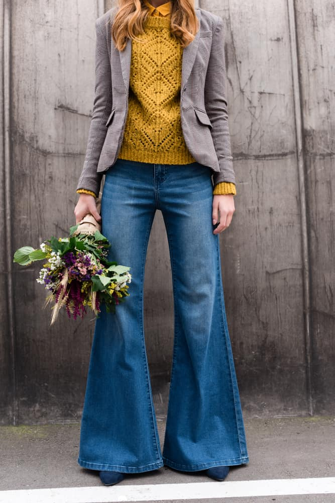 This is a close look at a woman wearing long flared denim jeans.