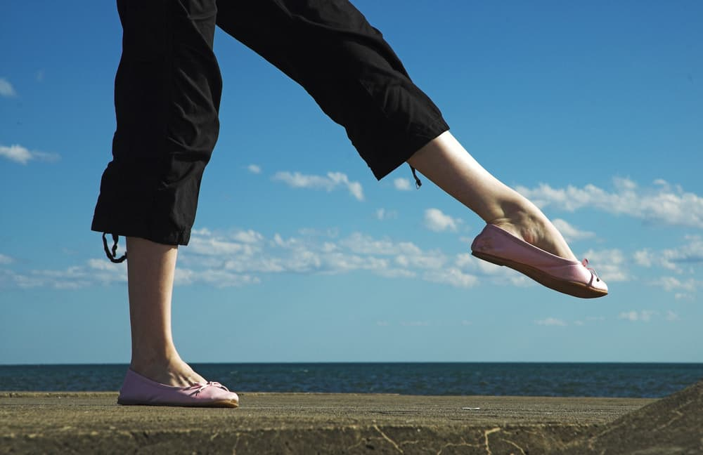 This is a close look at a woman wearing a pair of black carpi pants and a pair of pink flats.