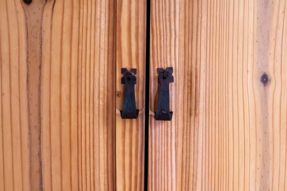 This is a close look at a wooden cedar wardrobe with iron pull handles on it.