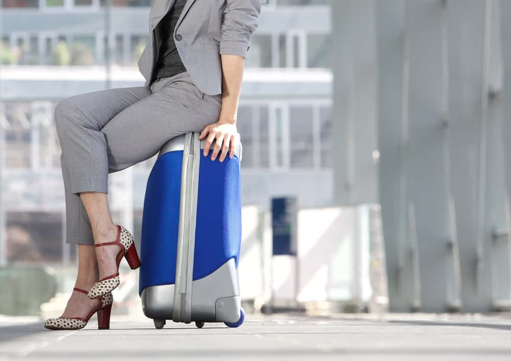 A woman sitting on her luggage wearing a cropped gray pantsuit.