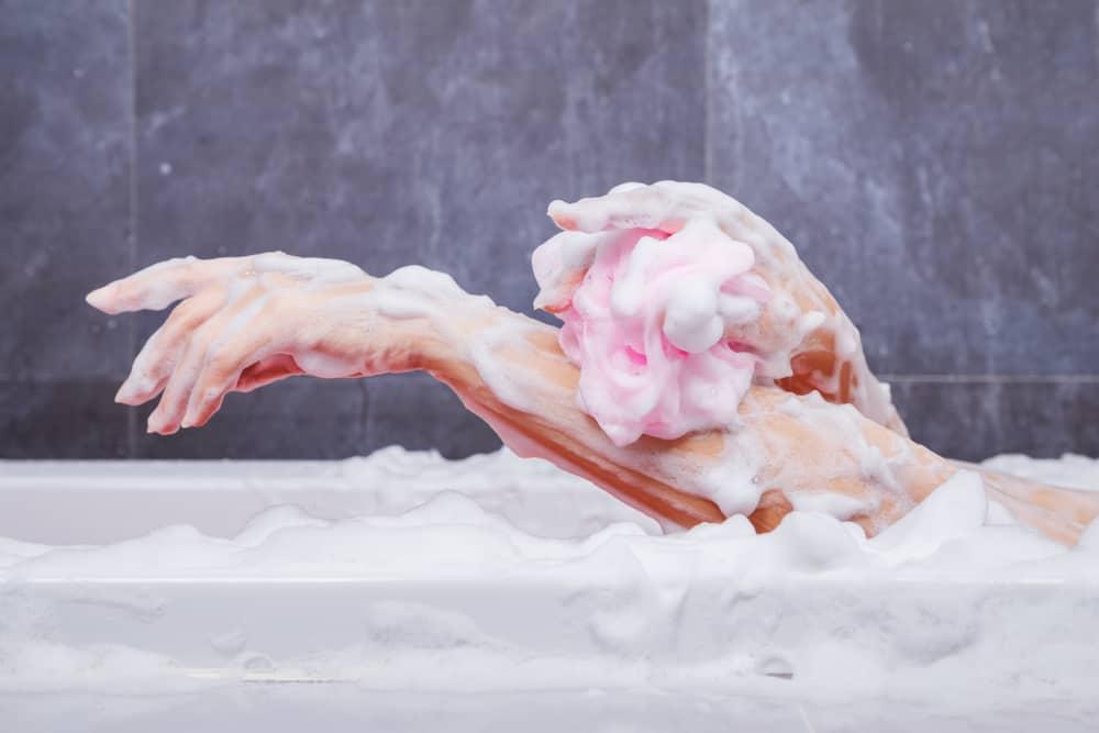 A woman using a bath sponge at the bathtub.