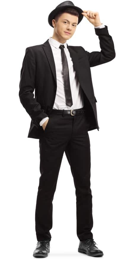 A man wearing a black suit and a matching black fedora.