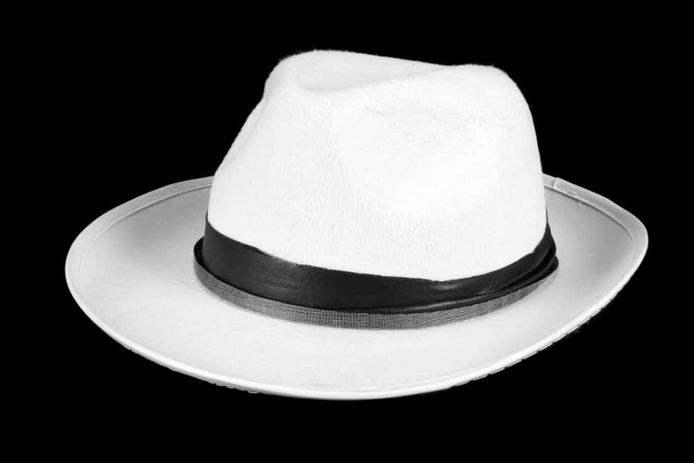 This is a white fedora on a black surface.
