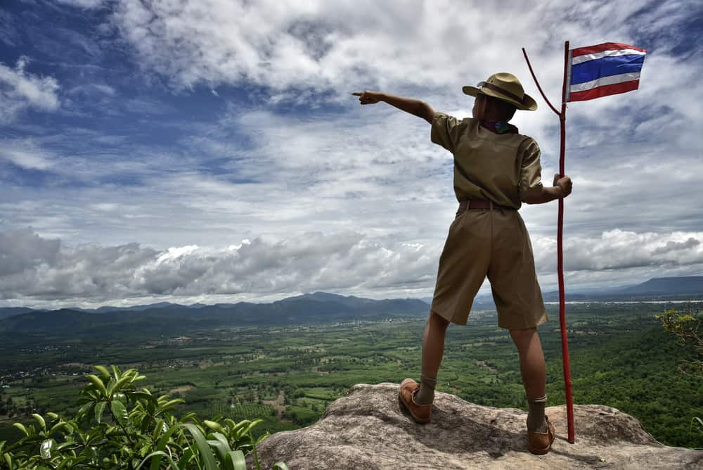 A boy scout standing on top of a hill.