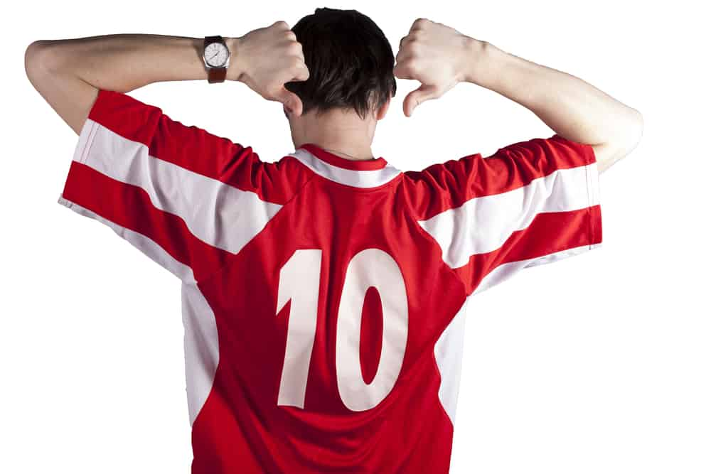 A man wearing a red jersey shirt with the number 10.