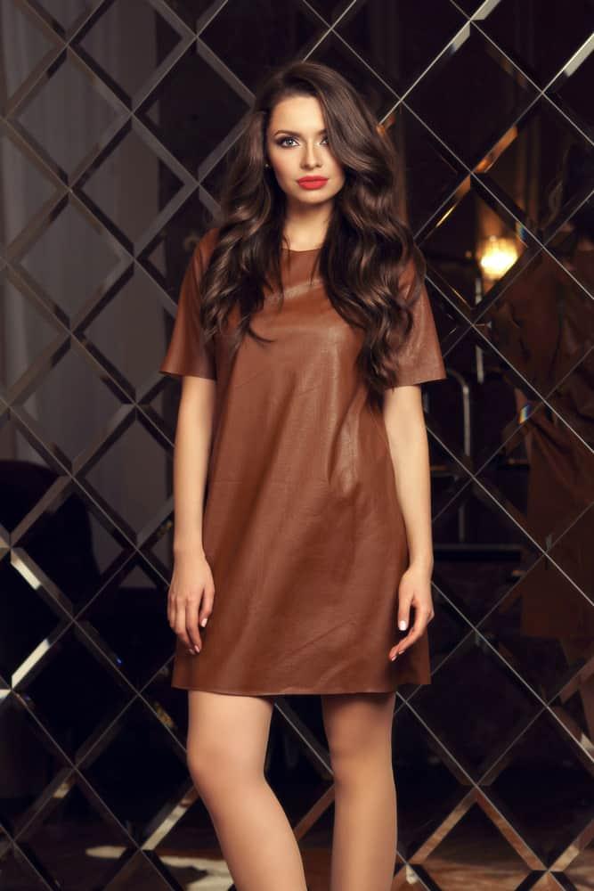 A woman wearing a brown shift dress.