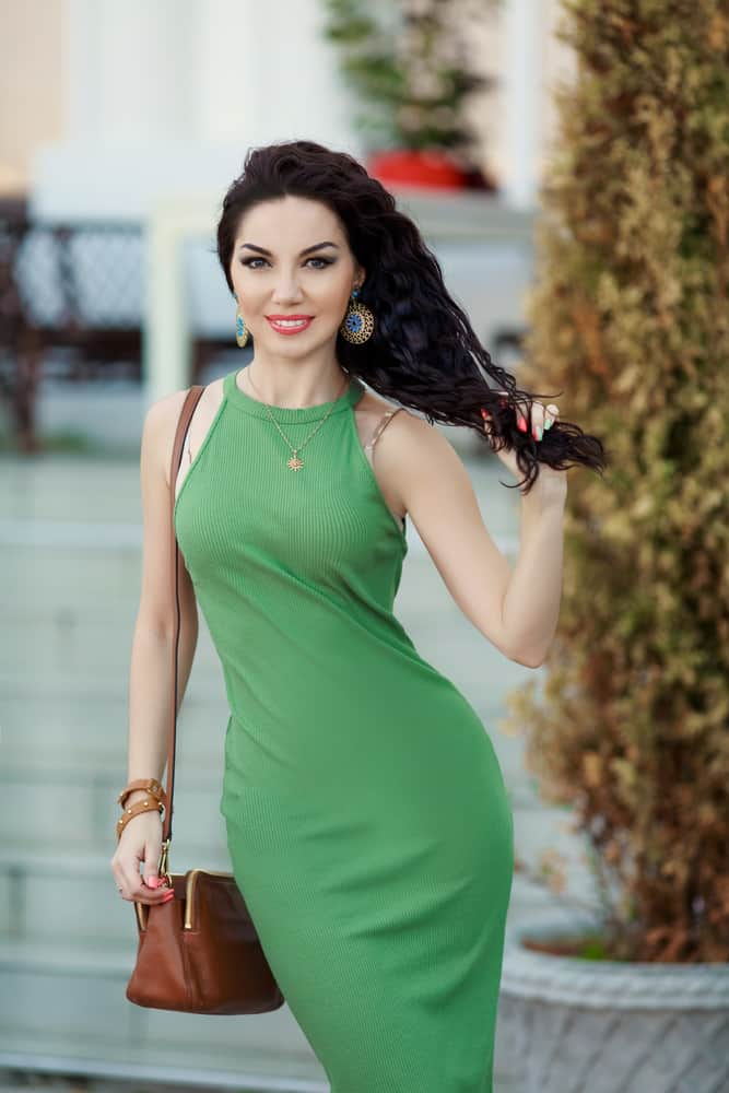 A close look at a woman wearing a green bodycon dress.