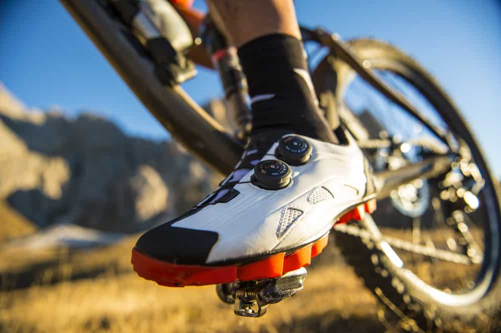 A close look at a cyclist wearing cycling shoes.