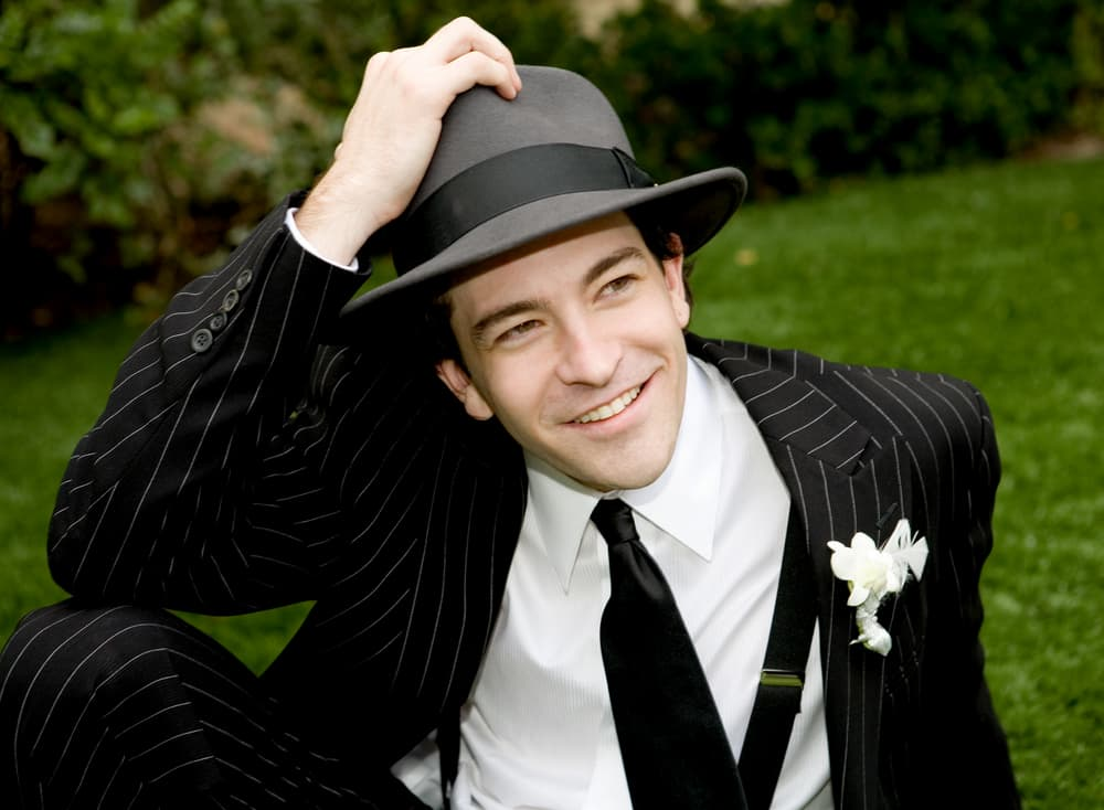 A man wearing a pin-striped suit with his fedora.