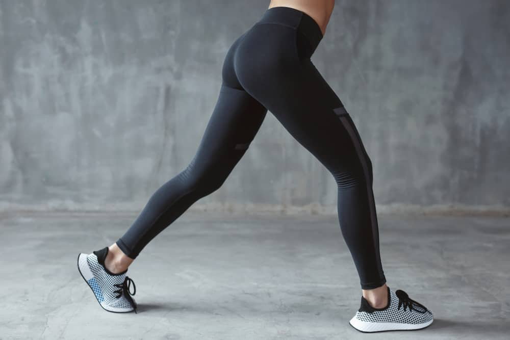This is a close look at a woman wearing a pair of sporty black leggings.
