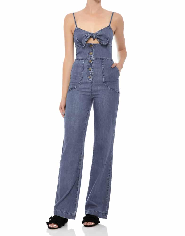 A close look at a woman wearing a one-piece denim jumpsuit.