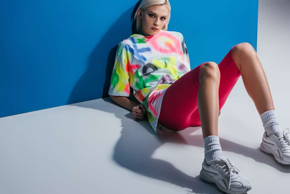 Model in a colorful graffiti shirt and pink bike shorts, poses against the blue wall.