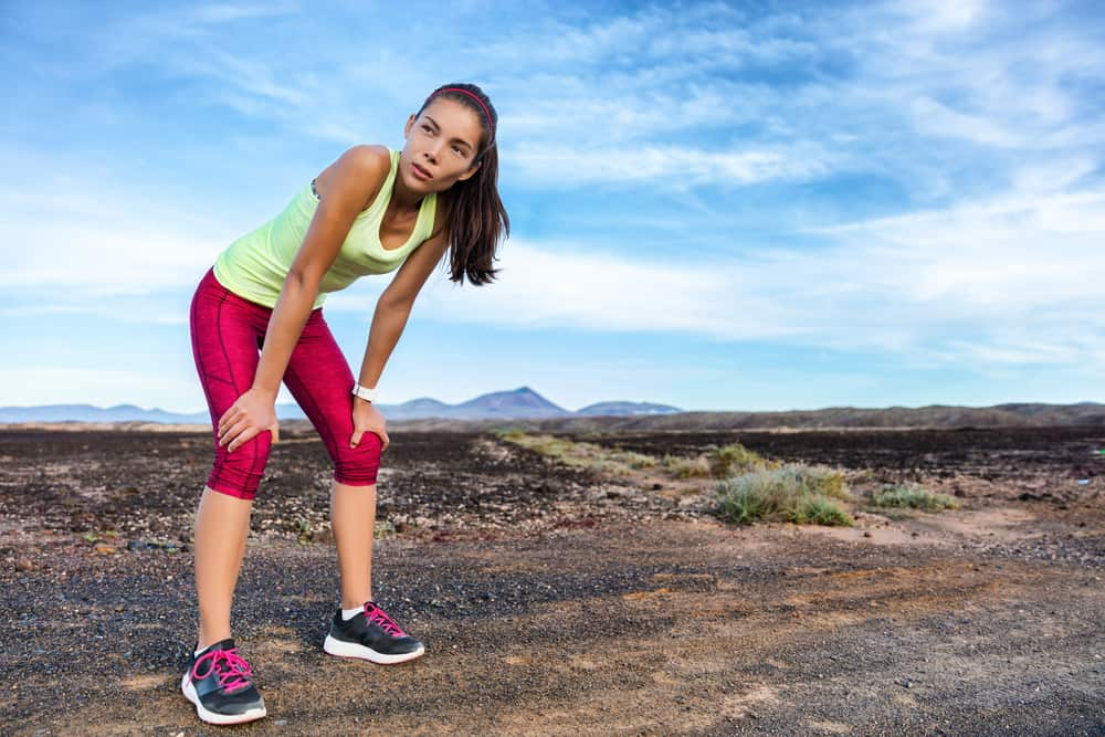 Woman in yellow tank top and pink capri leggings taking a break from running in a mountainous landscape.