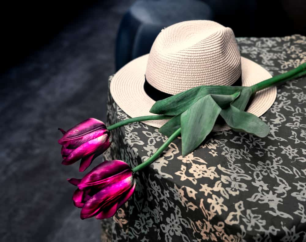 Chupalla hat and roses on top of a table.