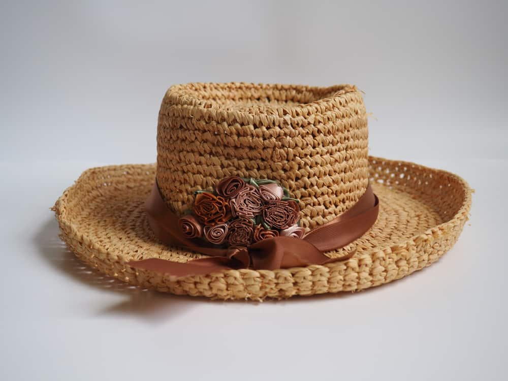 Chupalla hat adorned with brown ribbon and flowers.