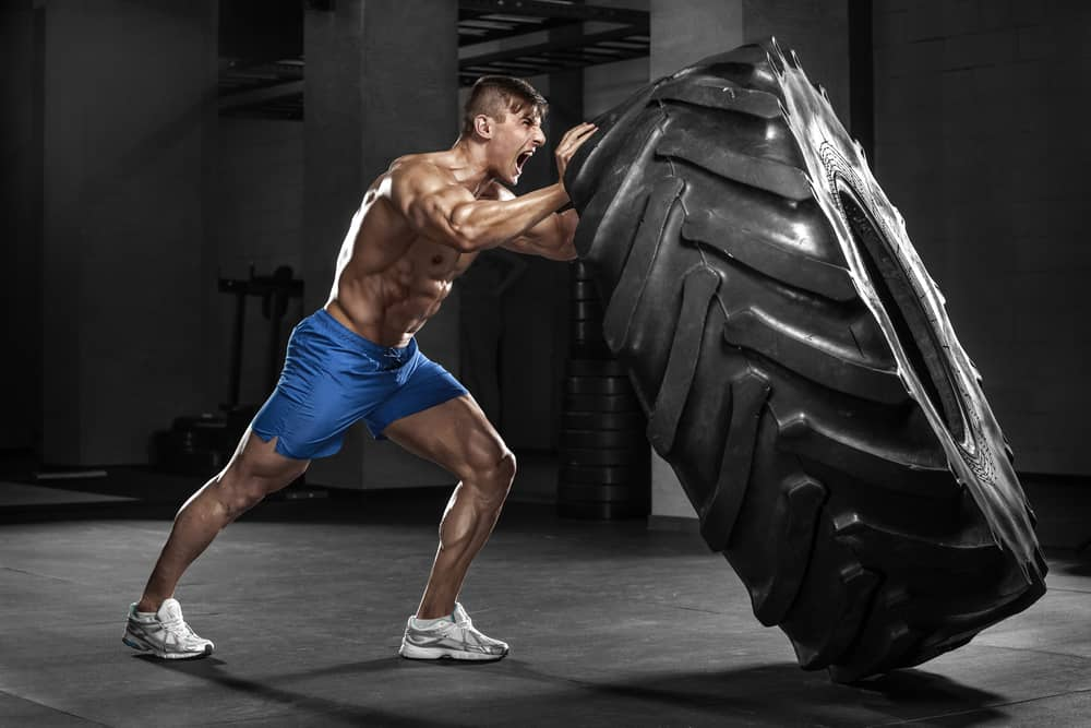 Muscular man flipping tire in a gym.