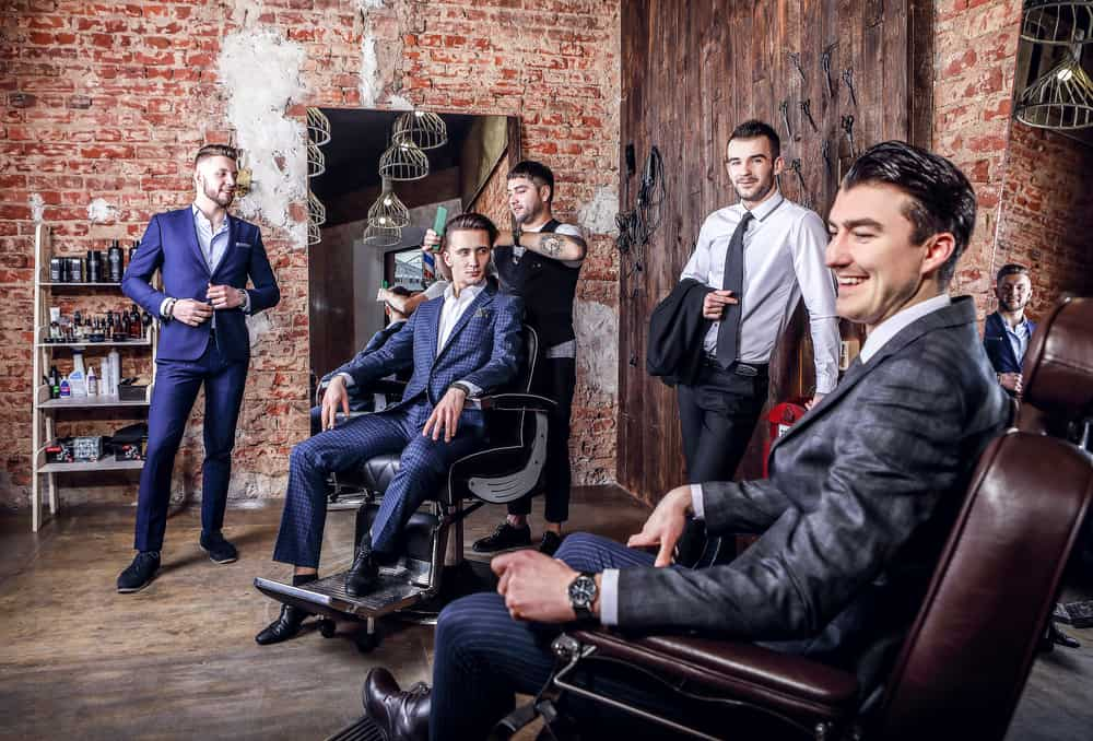 A group of men wearing suits inside the barbershop.