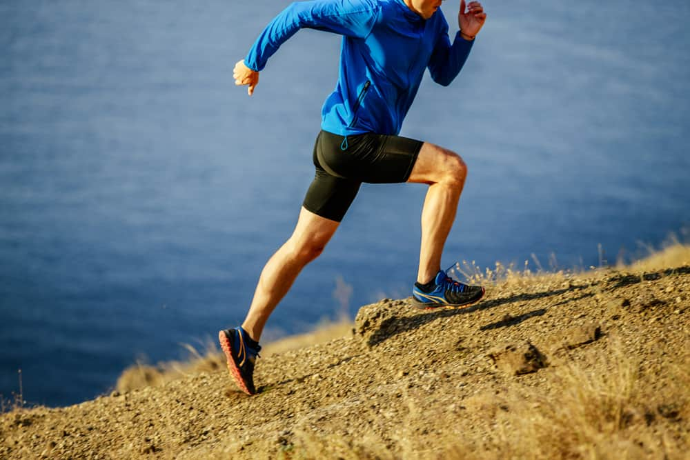 Man running on a steep slope of mountain.