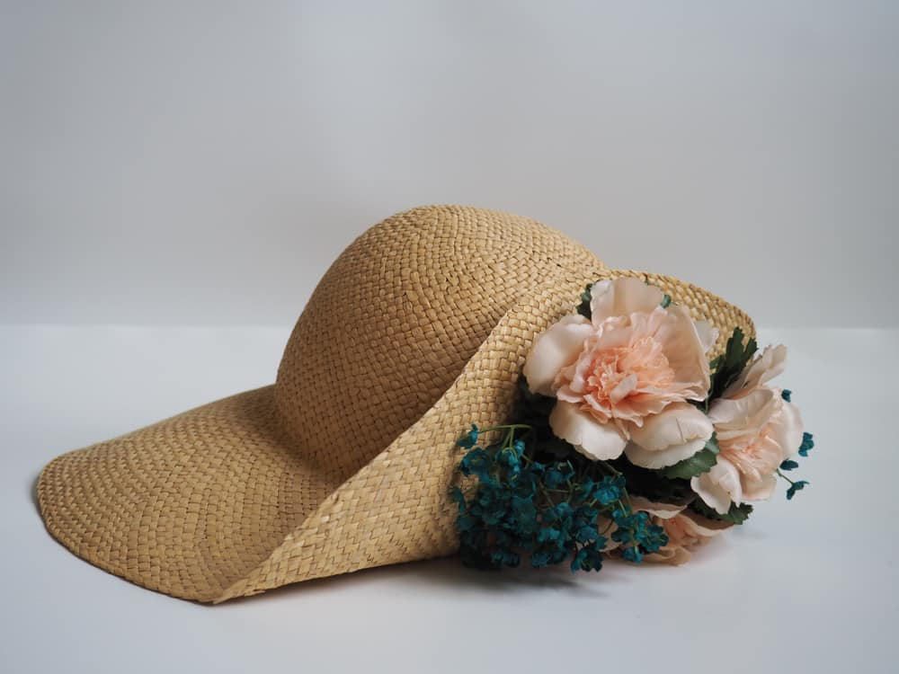 Shantung straw hat graced with peach flowers and blue leaves.