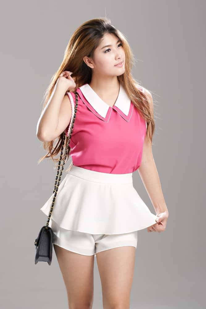 Woman wearing pink collared tank top with white double layer flutter skorts and shoulder bag.