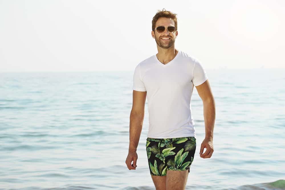 Man in a white shirt and black patterned swim shorts standing near the beach.
