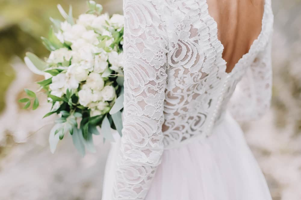 Back profile of a  bride in a lacy wedding dress holding a white bouquet.