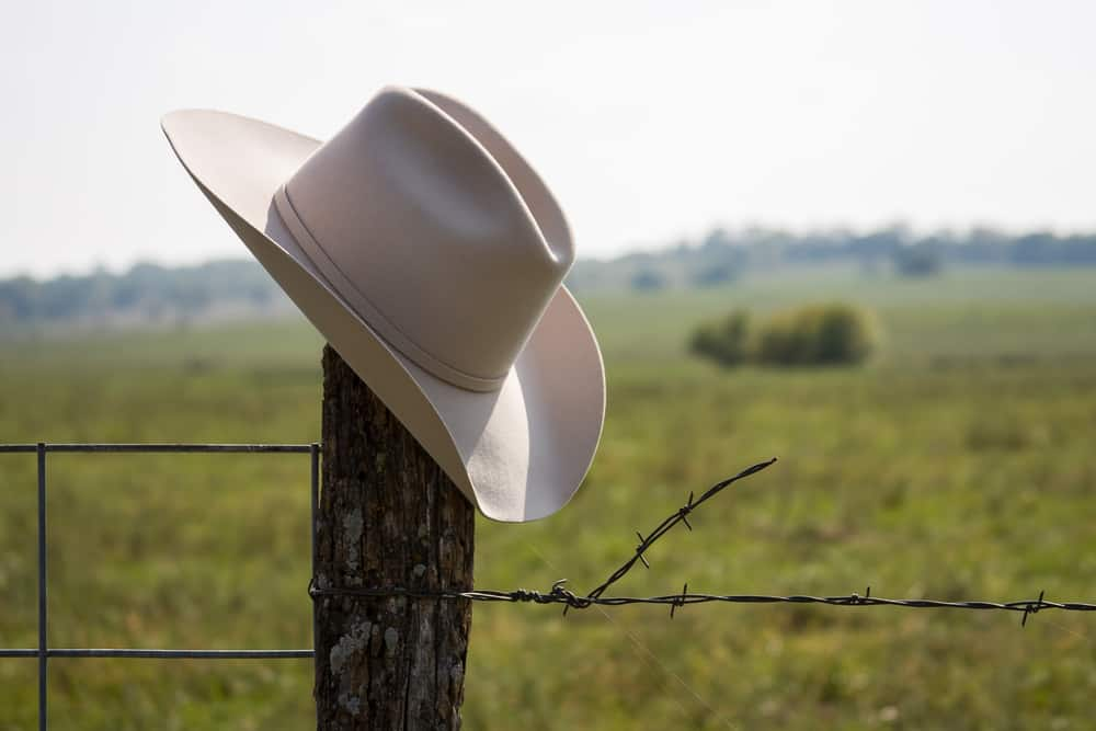 This is a close look at a beige cowboy hat on a wooden fence post.