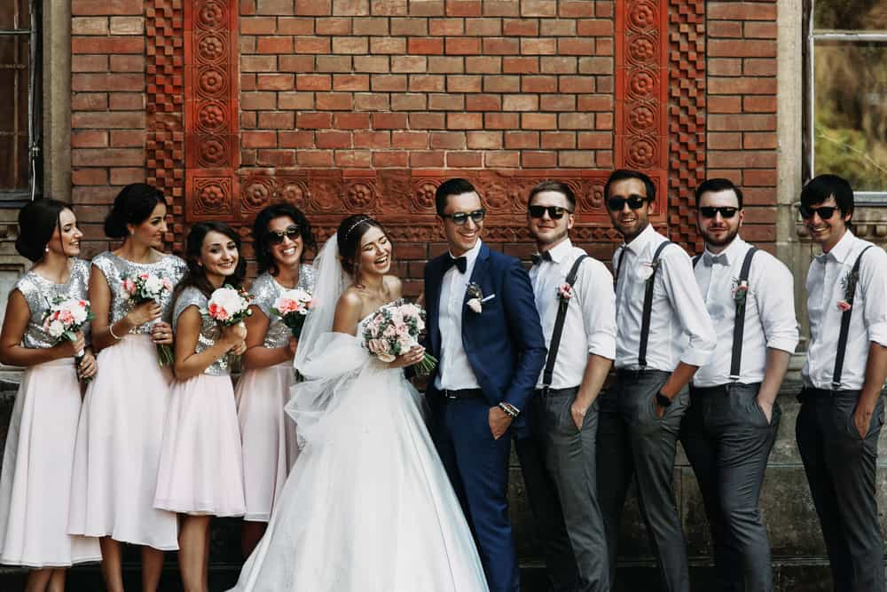 The bride and groom with their groomsmen wearing suspenders and bridesmaids wearing skirts.