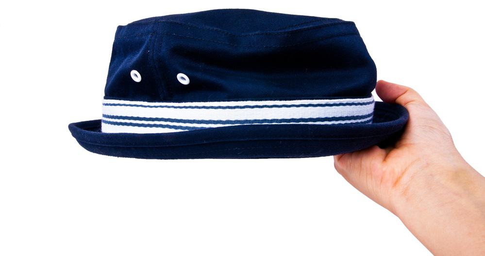 A hand holding up a vintage navy blue boater cotton fedora hat with a striped band.