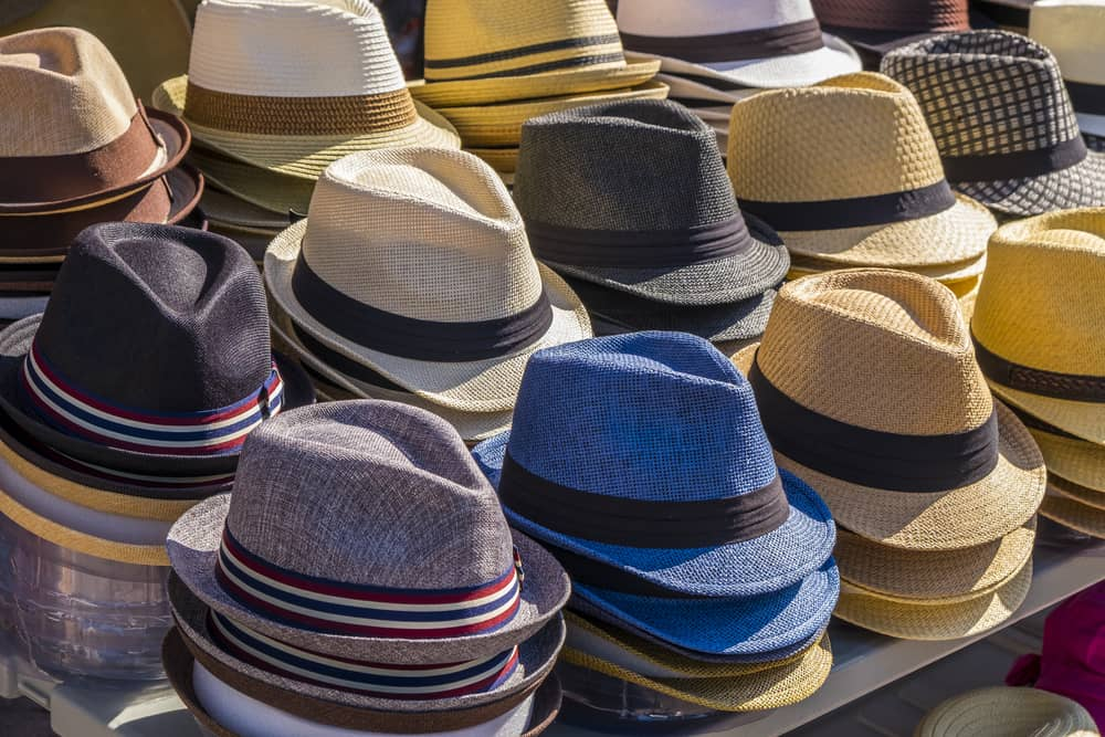 This is a close look at different fedoras on display at a market.