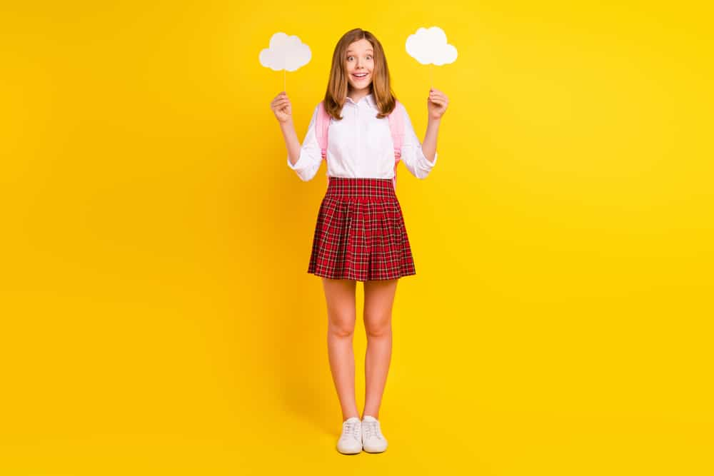 This is a girl wearing a red plaid bubble skirt and white blouse.