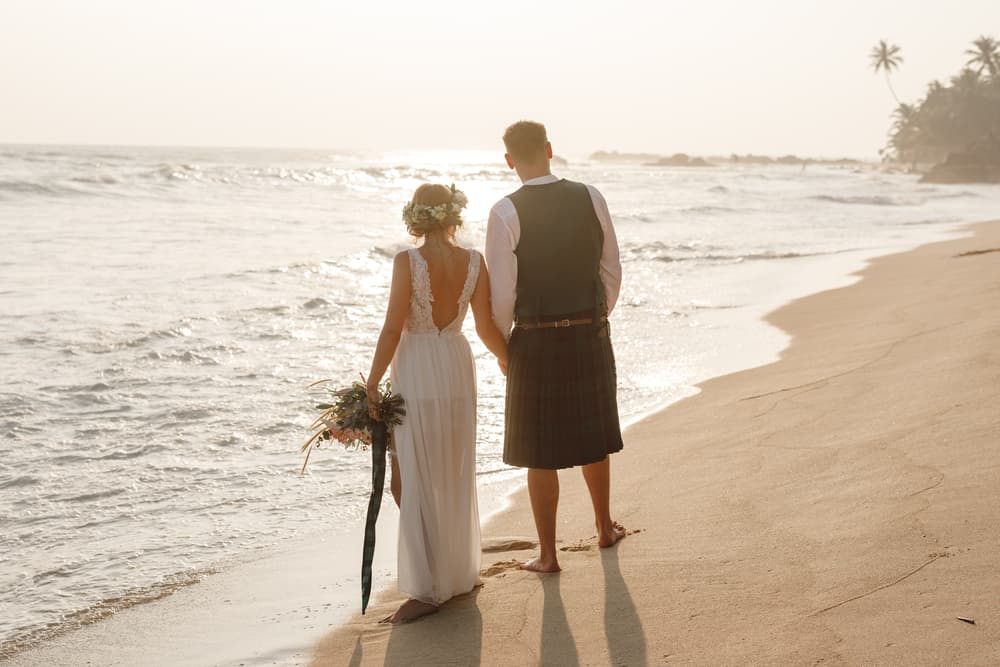The groom wearing a kilt and the bride wearing a dress at the beach.