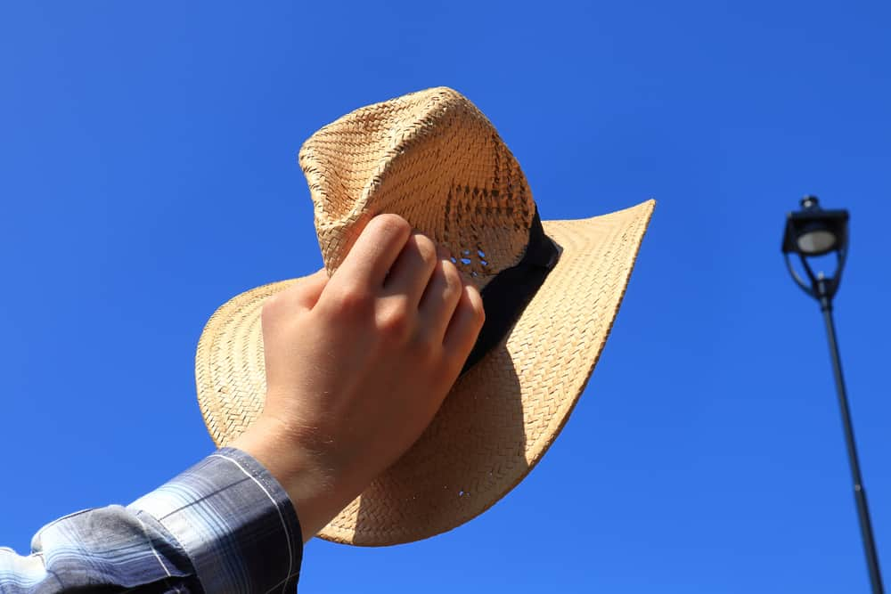 A man holding up a woven straw outback hat with a black band.