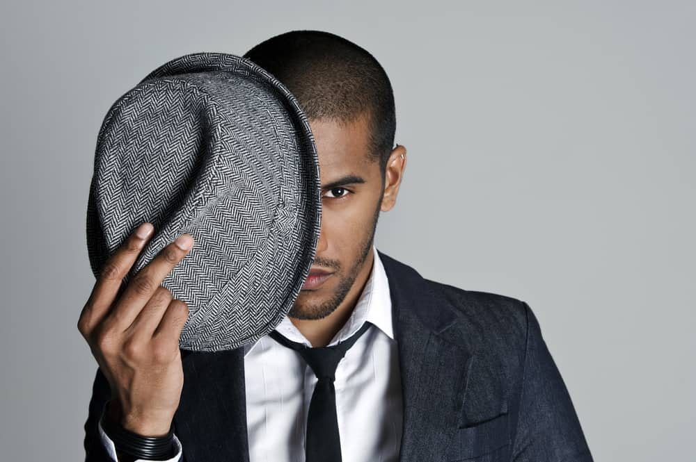 A man wearing a suit with a gray fedora hat.