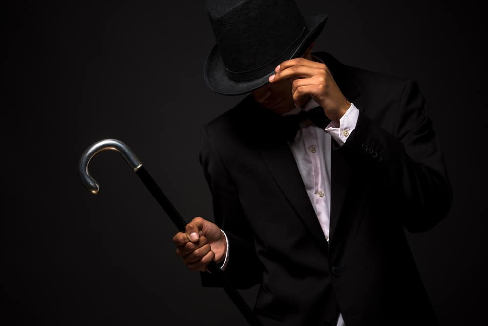 This is a man wearing a black tuxedo with a cane and a black top hat.