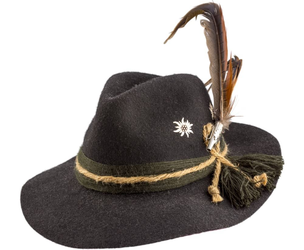 This is a close look at a tyrolean hat that has yarn bands and feathers.