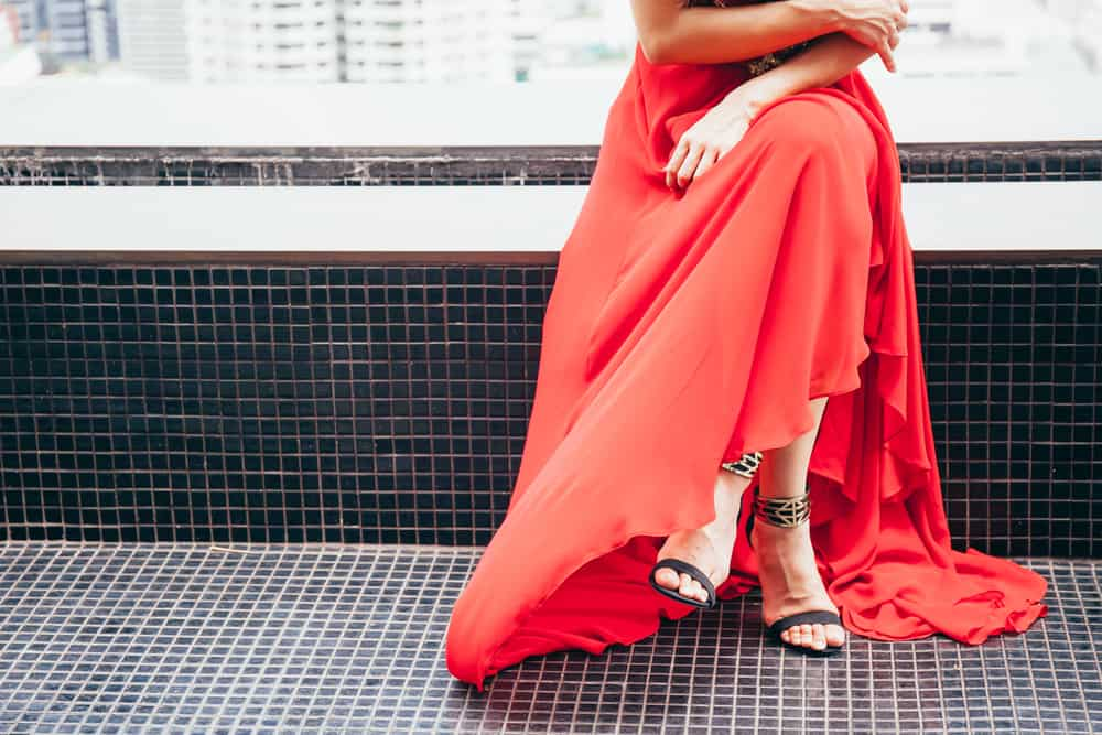A woman wearing a long red dress and strappy sandals.