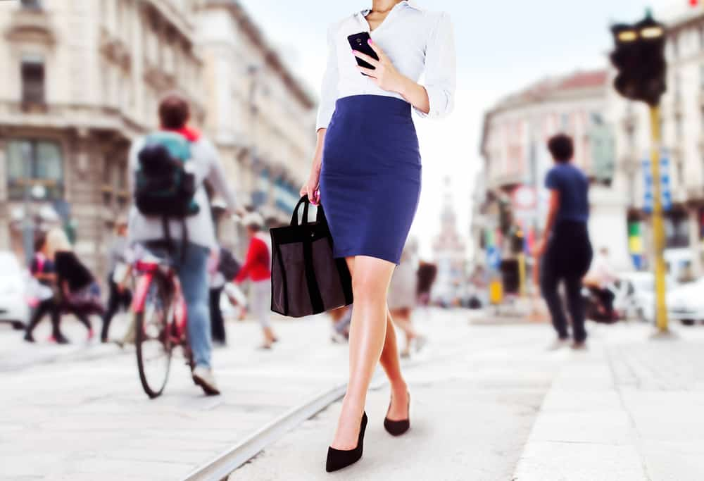 This is a woman on her way to the office wearing a blue pencil skirt and a white blouse.