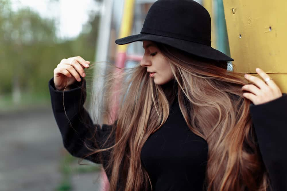 A woman wearing a black sweater and black fedora.