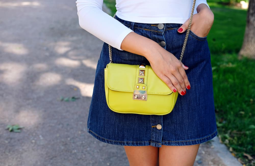 This is a close look at a woman wearing a jean skirt with a white long-sleeve shirt.