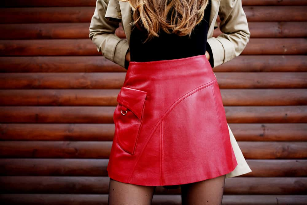 This is a close look at a woman wearing a red leather skirt.