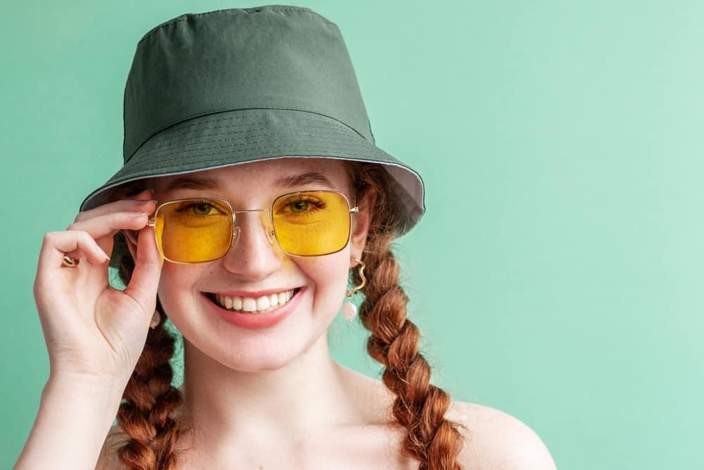 This is a woman with braids wearing a yellow pair of sunglasses and a green bucket hat.