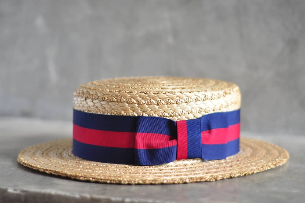 This is a close look at a woven straw boater hat with a red and blue band.